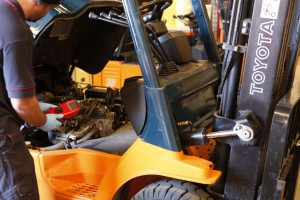toyota forklift service technician with meter