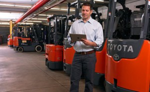 man with tablet near forklifts in warehouse